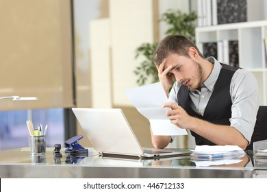 Sad businessman reading bad news in a letter sitting in a desk at office