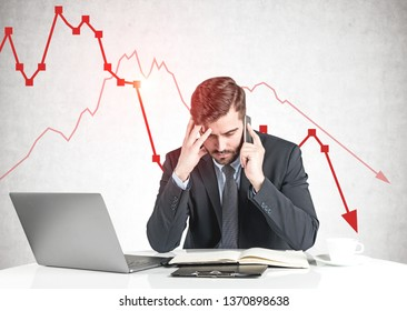 Sad businessman sitting at office table with laptop and talking on smartphone near concrete wall with declining graph. Financial crisis concept.