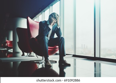 Sad businessman is sitting on red armchair and mourning for his dismissal after conversation with boss; man entrepreneur has just known about bankruptcy of his company and grieving over it