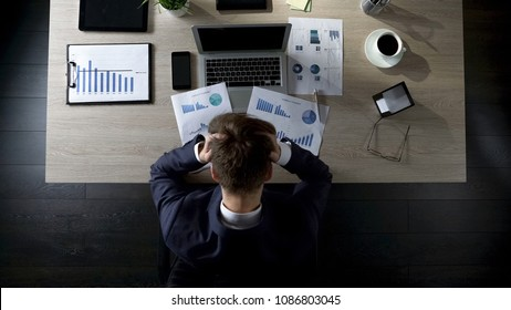 Sad businessman sitting at table and thinking about debts, bankruptcy, top view