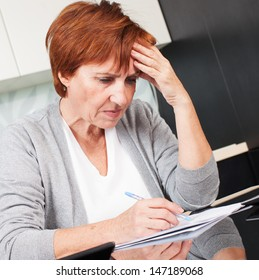 Sad businesswoman with document. Elderly woman writing a letter