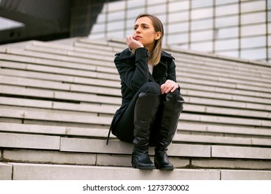 Sad businesswoman sitting on the staircase in the city.Toned image.