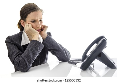 Sad businesswoman sitting at white office desk waiting for a phone call.