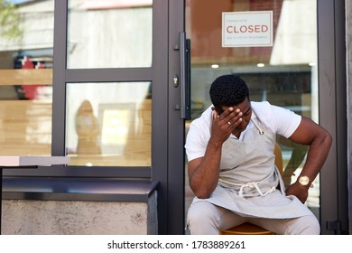 sad cafe owner sit outdoors, his cafe restaurant is closed, has no clients due to coronavirus pandemic, crisis concept