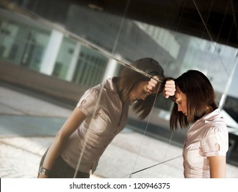 sad caucasian business woman banging her head against a wall out of office building. Reflection on wall
