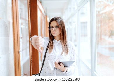 Sad Caucasian collage girl showing thumbs down for failing exams while standing next to noticeboard in hallway. University building interior.