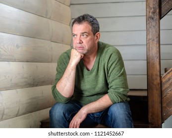 Sad Caucasian middle-aged man sitting on the stairs inside the house
