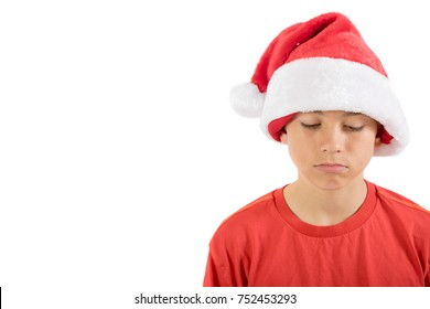 Sad caucasian teenage boy wearing a Christmas hat, isolated on white background