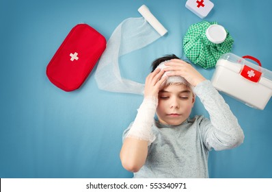 Sad child in bandages lying in bed. Wounded boy on blue background with first aid accessories.
