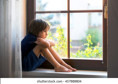 Sad child, boy, sitting on a window shield, watching the sunset