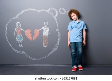 Sad child with broken heart. Boy is disappointed of parents' divorce, staying near a gray wall.
