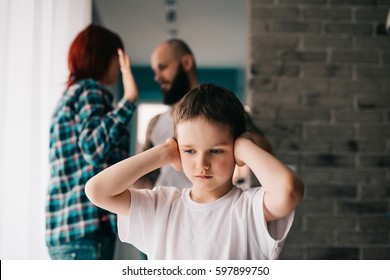 Sad child covering his ears with hands during parents quarrel. Man about to beat his wife