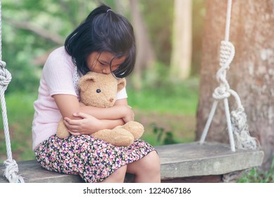 Sad child with Family problem,holding teddy bear on wooden swing in park.Asian little girl sitting with best friend forever,sad moment.Teddy Bear is a gift,toy and best friend for children.