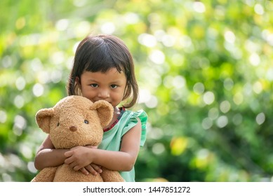 Sad child with Family problem,violence of parent is the one of divorce in bad relation family.Stress kid hugging teddy bear in park.Teddy Bear is a gift,toy and best friend for children.