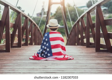 sad child with the flag of the United States on wooden bridge