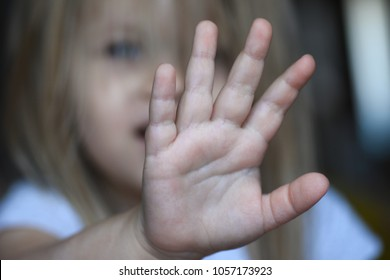 Sad child girl covers her face with her hand from violence