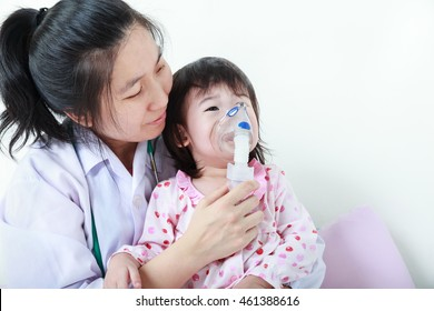 Sad child having respiratory illness helped by health professional with inhaler. Pediatrician take care asian girl with asthma problems making inhalation with mask on her face at hospital. Child cry.