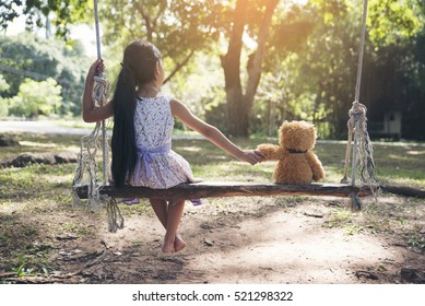 Sad child holding hand with teddy bear on wooden swing in park. Asian kid sitting with best friends forever, sad moment. Teddybear is a gift, toy and best friend for children. Friendship concept