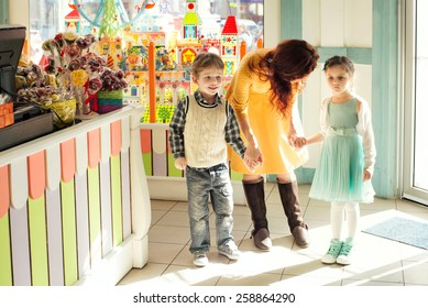 Sad child holding mother by the hand in the children's store. Son and daughter holding mother for her  hand