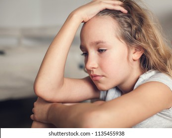Sad child at home. Abuse. Depression girl indoors