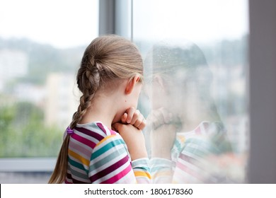 Sad child looking through rainy window at home. Upset kid in self isolation during quarantine. Lifestyle, authentic, candid moment.