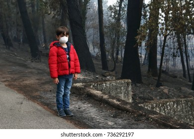 sad child with mask looking the burned forest after a devastating wildfire in Galicia