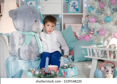 Sad child on the background of a Christmas tree. Six year old boy with a huge teddy bear toy