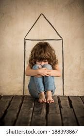 Sad child sitting on the floor. Homeless kid in dark room