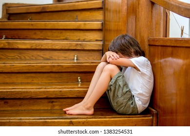 Sad child, sitting on a staircase in a big house, concept for bullying, depression stress or frustration
