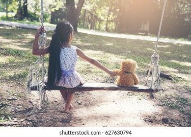Sad Child sitting with teddy bear.Cute little girl shook hands with a teddy bear on a wooden swing in park.Friendship concept.