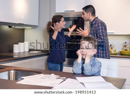 Sad child suffering and his parents having hard discussion in a home kitchen by couple difficulties. Family problems concept.