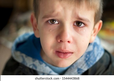 Sad child who is crying. A child with tears in his eyes looking at the camera. Close up