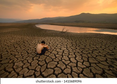 Sad Children or young man sitting on cracked earth near drying river metaphor water crisis, climate change, Drought and Environment disaster