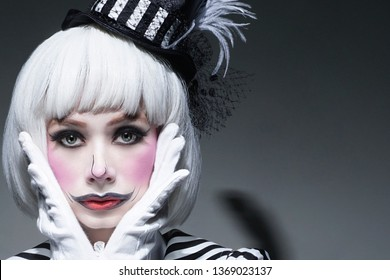 Sad clown make-up with uncombed white hair.Pensive woman in Halloween clown costume. Masquerade girl with vintage dress. Clown on gray background.