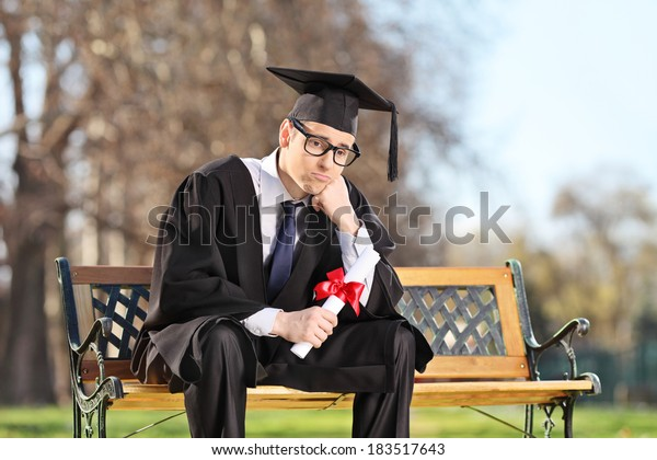 Sad college student sitting on a bench in park