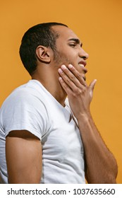 Sad concept. Sad Afro-American is having toothache. Young emotional man. Human emotions, facial expression concept. Profile . Studio. Isolated on trendy orange