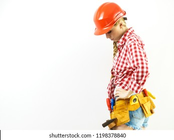 Sad construction worker woman wearing toolbelt and red helmet standing against white isolated background.