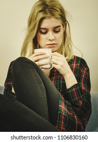 Sad contemplating woman sitting on couch alone drinking tea of coffee from mug.