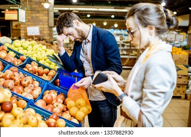 Sad couple with despired emotions having a problem with their budget buying food in the supermarket