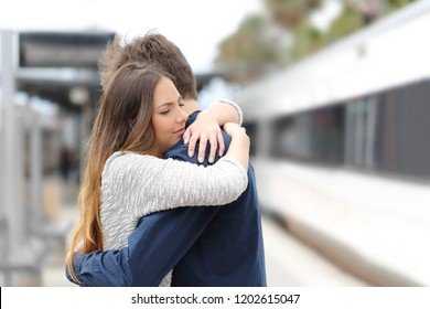 Sad couple hugging saying goodbye before train travel