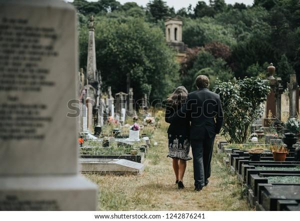 Sad couple walking through a cemetery