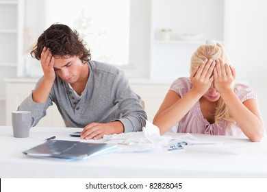 Sad couple while accounting in their living room