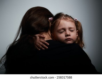 Sad crying daughter hugging her mother with sad face on dark shadows background