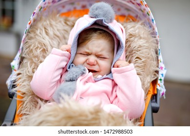 Sad crying little beautiful baby girl sitting in the pram or stroller on autumn day. Unhappy tired and exhausted child in warm clothes, fashion stylish pink baby coat with bunny ears.