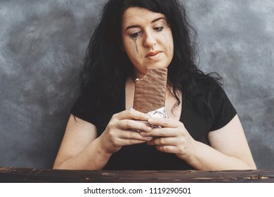 Sad crying young woman tired of diet restrictions eating chocolate. Weight loss, sugar addiction, stress, nutrition, people emotions