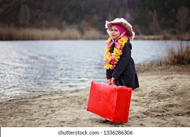 Sad cute 5-6 years old girl in a coat and flowers garland staying on a beach, outdoor, ready for summer, holiday and travel concept