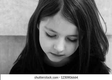 Sad cute, pretty, girl, child, kid with depress eyes on adorable face and long, brunette hair sitting on beige background. Loneliness, melancholy and boredom