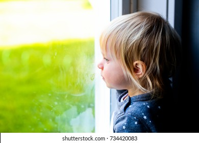 Sad Cute Toddler Girl Looks at the Window with Hope