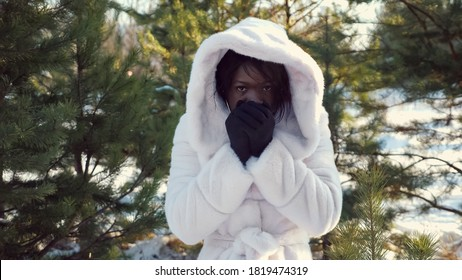 sad dark-skinned girl in hood trembles with cold and warms hands against green pine-trees in cold winter closeup