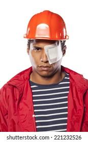 sad dark-skinned worker with helmet and injured eye